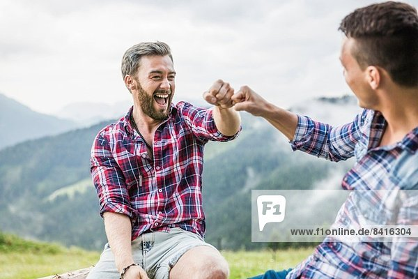 Two male friends sitting on fence  Tyrol Austria