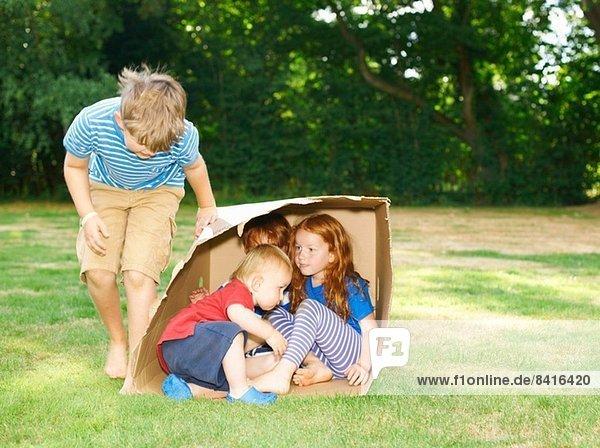 Siblings hiding in cardboard box in garden