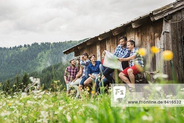 Gruppe von Freunden beim Chatten und Kartenlesen  Tirol  Österreich