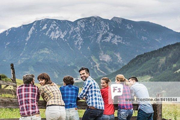 Rückansicht der Gruppe von Freunden  die die Aussicht genießen  Tirol  Österreich