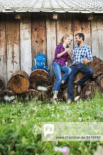 Paar sitzt auf geschnittenen Stämmen mit Wein