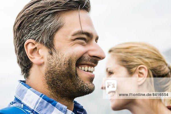 Paar lächelnd und in entgegengesetzte Richtungen blickend