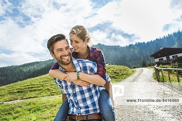 Frau reitet Huckepack auf Mann  Tirol  Österreich
