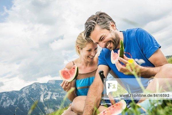 Pärchen essen Wassermelone beim Picknick