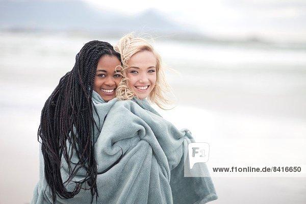Schwules Paar in Decke gehüllt am Strand