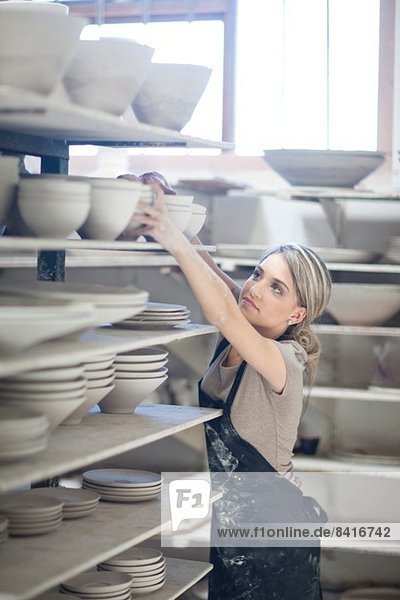 Potter stacking bowls onto shelf at crockery factory