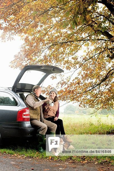 Seniorenpaar mit Hunden  die sich Kaffee aus dem Kofferraum teilen  Norfolk  UK