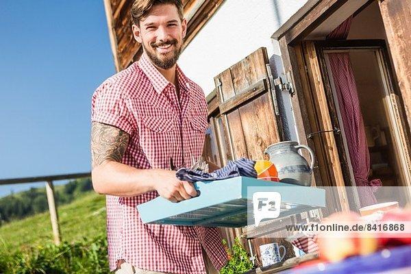 Junger Mann mit Tablett außerhalb des Chalets  Tirol  Österreich Junger Mann mit Tablett außerhalb des Chalets, Tirol, Österreich