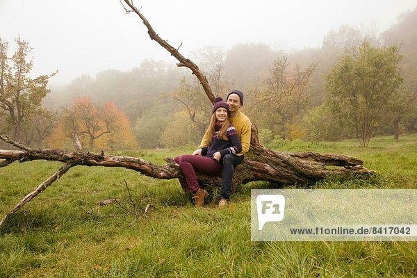 Young couple sitting on bare tree in misty park