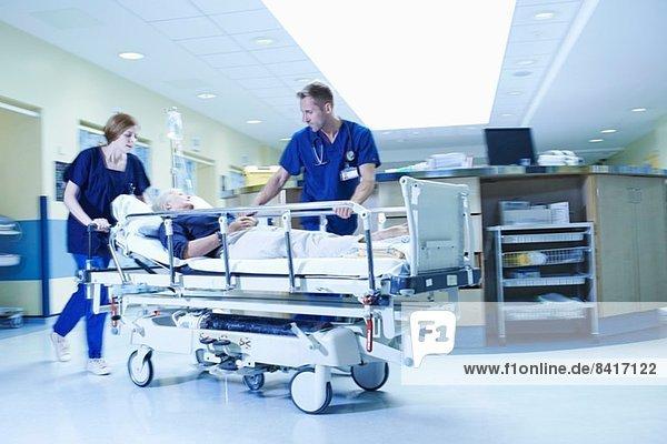 Zwei Sanitäter stürmen mit Trage in der Notaufnahme des Krankenhauses