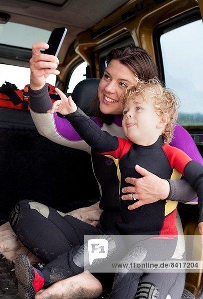 Mutter und Sohn im Auto mit Smartphone