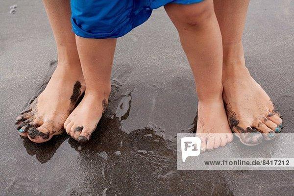 Mutter und Sohn auf nassem Sand stehend