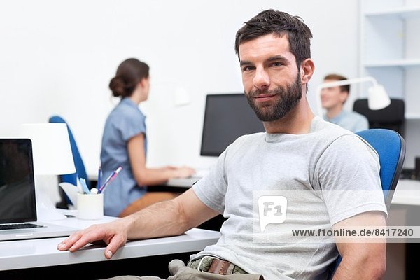 Mid adult man sitting at desk in office