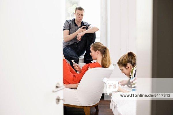 Drei junge erwachsene Freunde mit Handy und digitalem Tablett im Schlafzimmer