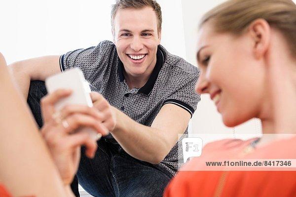 Junges erwachsenes Paar lacht über Handy