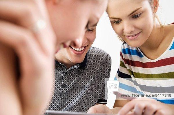 Nahaufnahme von drei jungen erwachsenen Freunden beim Betrachten des digitalen Tabletts
