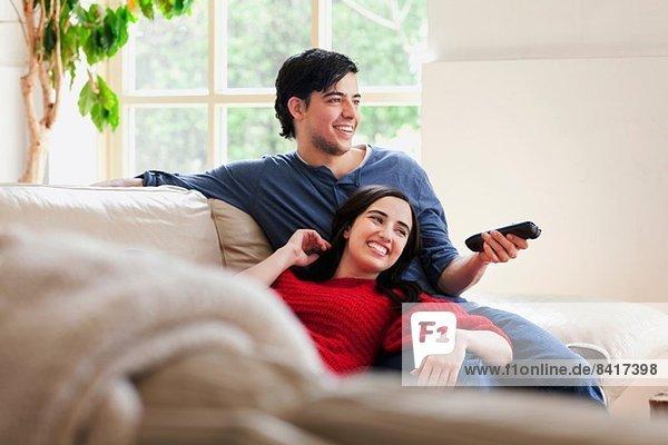 Junges Paar beim Fernsehen auf dem Wohnzimmersofa
