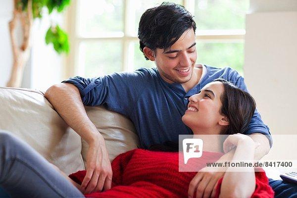 Junges Paar auf dem Wohnzimmersofa liegend