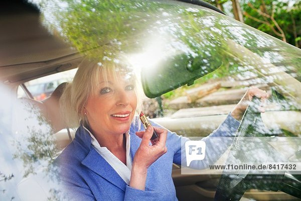 Reife Frau mit Lippenstift im Auto