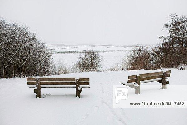 Zwei ländliche Parkbänke mit Blick auf die verschneite Landschaft