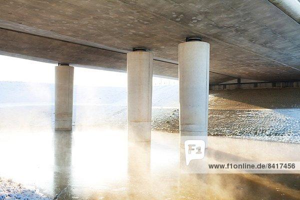 Transportbrücke über nebligen Fluss im Winter
