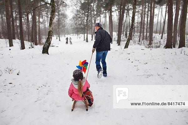 Vater zieht Tochter auf Schlitten im Schnee