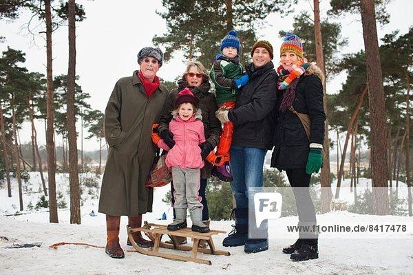 Familienporträt von drei Generationen in der Winterlandschaft