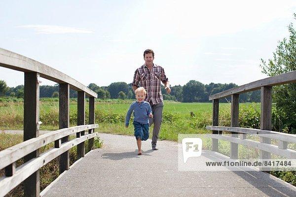 Vater und Sohn laufen über Holzbrücke