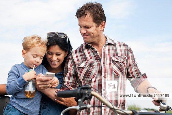 Familie  die ein Smartphone anschaut und einen Drink zu sich nimmt
