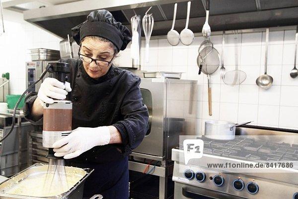 Frau  die in der Restaurantküche arbeitet