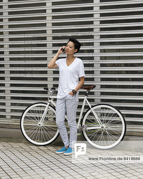 Young woman leaning against bicycle  using smartphone