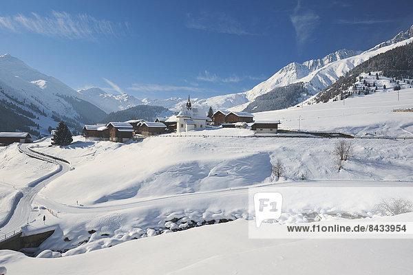 Europa Berg Winter Wohnhaus Gebäude Bach Dorf Scheune Kanton Graubünden Kapelle Sedrun Schnee Schweiz Weg