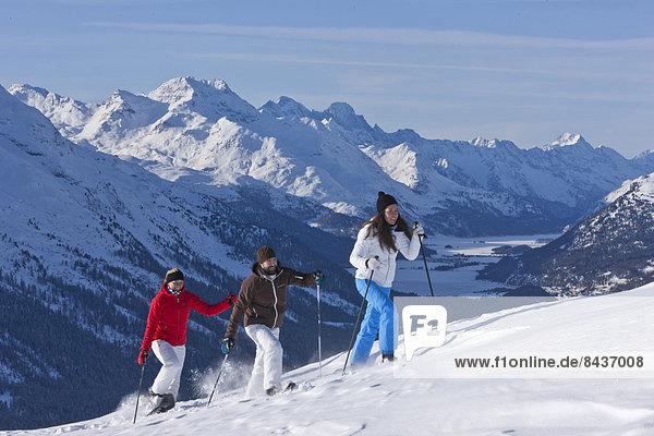 Switzerland  Europe  mountain  mountains  winter  canton  GR  Graubünden  Grisons  Engadin  Engadine  Upper Engadine  winter sports  snow shoe  hiking  Muottas Muragl  group  woman  man  three  snow  walking