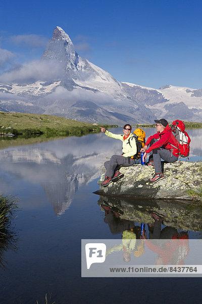 Frau Mann gehen Spiegelung See wandern Matterhorn Bergsee