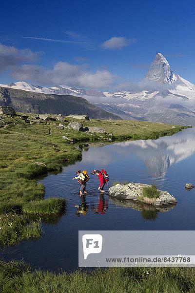 Switzerland  Europe  canton  Valais  walking  hiking  couple  man  woman  mountain lake  lake  reflection  Matterhorn  Zermatt  Stellisee
