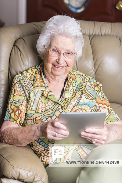 Lächelnde alte Frau beim Blick auf den Tablet-Computer