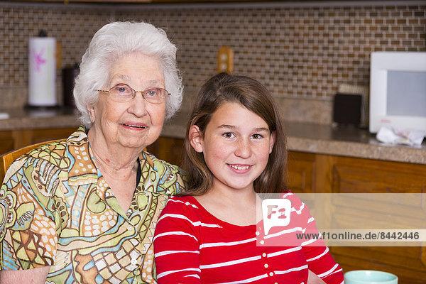 Alte Frau und ihre Urenkelin sitzen Seite an Seite