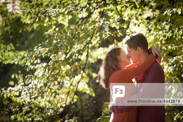 Happy young couple enjoying autumn in a park