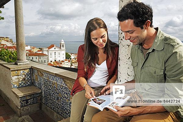 Portugal  Lisboa  Alfama  Miradouro de Santa Luzia  junges Paar mit Reiseführer