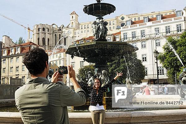 Portugal  Lisboa  Baixa  Rossio  Praca Dom Pedro IV  junges Paar fotografiert vor einem Brunnen