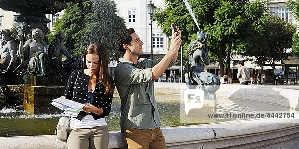 Portugal  Lisboa  Baixa  Rossio  Praca Dom Pedro IV  young couple with city map and smart phone in front of a fountain