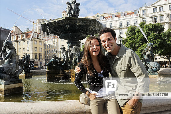 Portugal  Lisboa  Baixa  Rossio  Praca Dom Pedro IV  lächelndes junges Paar vor einem Brunnen