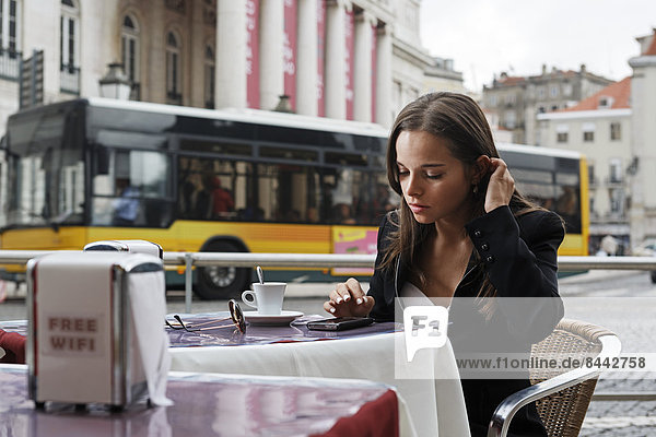 Portugal  Lisboa  Baixa  Rossio  Praca Dom Pedro IV  Teatro Nacional  junge Frau mit Smartphone im Straßencafé