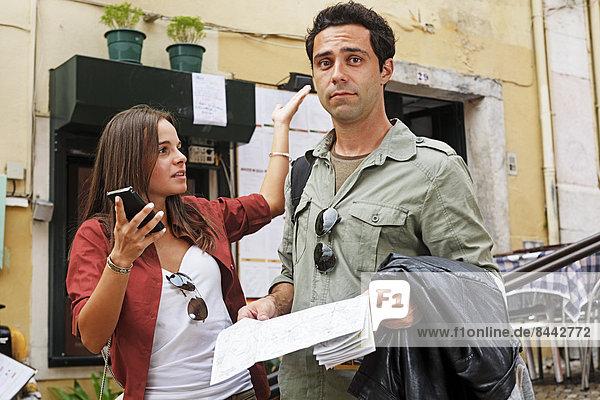 Portugal  Lisboa  Carmo  Calcada du Duque  junges Paar mit Stadtplan und Smartphone bei der Orientierung