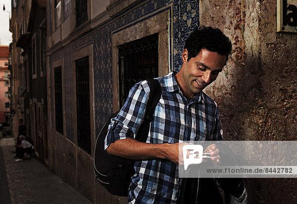 Portugal  Lisboa  Bairro Alto  junger Mann beim Blick auf sein Handy