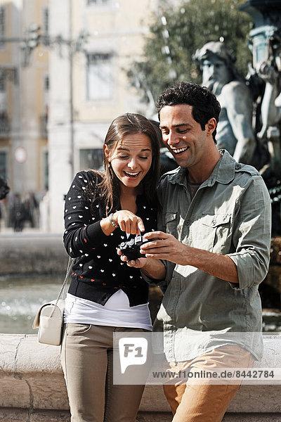 Portugal  Lisboa  Baixa  Rossio  Praca Dom Pedro IV  lächelndes junges Paar beim Betrachten eigener Bilder