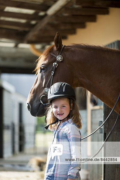 Kleines Mädchen mit Pferd im Stall