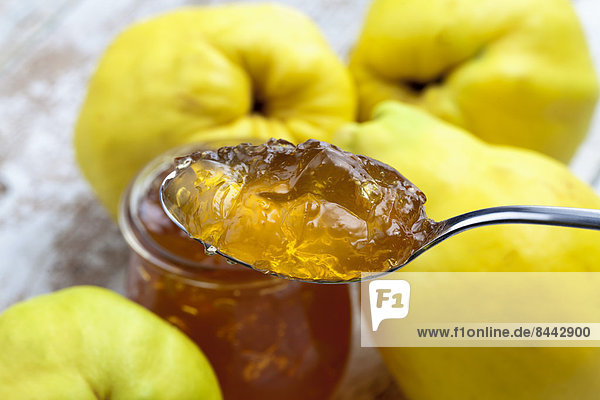 Four quinces (Cydonia oblonga)  a spoon and a glass of quince marmalade on wooden table