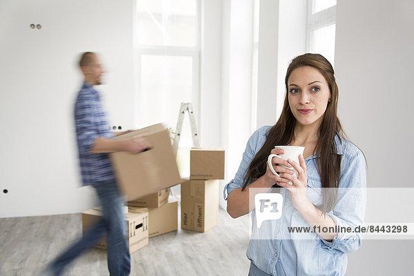 Junges Paar  das in ein neues Zuhause zieht  Frau mit einer Tasse Kaffee