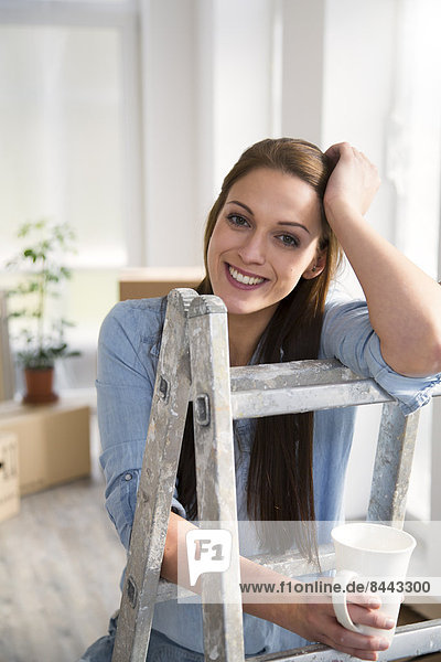 Young woman in new home having a coffee break